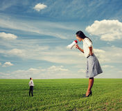 Angry woman and small man on the field Royalty Free Stock Photos