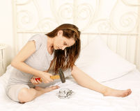 Angry woman smashing alarm clock Royalty Free Stock Photography