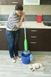 Angry woman squeezing mop near puppy Royalty Free Stock Photography