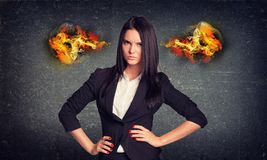 Angry woman standing with arms akimbo, fire from. Angry businesswoman standing with arms akimbo, fire from ears. Concrete wall in background Royalty Free Stock Photos