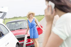Angry woman standing by damaged cars with female using cell phone in foreground Royalty Free Stock Photos