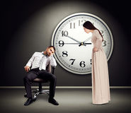 Angry woman staring at lazy man Stock Photo
