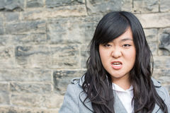 Angry woman by a stone wall Stock Photos