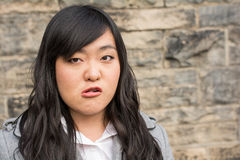 Angry woman by a stone wall Stock Photography