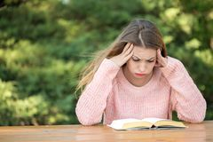 Angry woman studying outside. Beautiful woman studying outside in a park with a frowned face Royalty Free Stock Photos