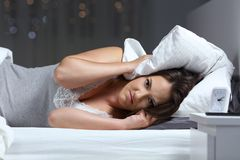 Angry woman suffering for neighbour noise. And looking at camera lying on a bed in the night at home royalty free stock photography