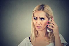Beautiful angry woman talking on her cell phone on a gray background. Angry woman talking on her cell phone on a gray background Stock Photography