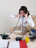 Angry woman talking on the phones. Stressed secretary in the office talking on two phones Stock Photography