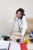 Angry woman talking on the phones. Whacked by problems lady sit on table and talking by phones Royalty Free Stock Images
