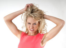 Angry woman tearing hair. Angry blond woman with hands in her hair Stock Images