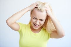 Angry woman tearing her hair in frustration Stock Photo