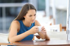 Angry woman thinking in a coffee shop terrace. Single angry woman thinking and holding a cup sitting in a bar terrace stock image