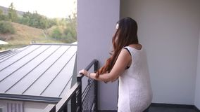 Angry woman is throwing male clothing out of the balcony while her man is picking them up outside.