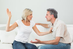 Angry woman about to slap a man at home Royalty Free Stock Image