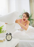 Angry woman trying to break alarm clock by pillow Royalty Free Stock Photo
