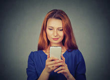 Angry woman unhappy, annoyed by something on cell phone texting receiving bad sms message Stock Photo
