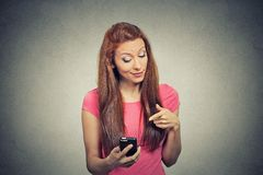 Angry woman unhappy, annoyed by something on her cell phone texting Stock Photo