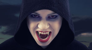 Angry woman vampire. Against the dark sky Stock Photo
