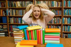 Angry woman yelling, Caucasian girl with long hair, screaming with fury in the library. Angry woman yelling, caucasian girl with long hair screaming with rage stock images