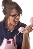 Angry woman yells into the telephone Stock Photos