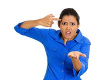 Angry woman, are you crazy. Closeup portrait of an angry pretty young woman gesturing with her finger against temple asking are you crazy? Isolated on white Royalty Free Stock Photos