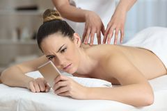 Angry woman receiving a message during massage. Angry women receiving a phone message during a therapeutic massage Stock Photos