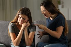 Angry woman scolding her sad friend. Angry women scolding her sad friend sitting on a couch in the living room at home Stock Image