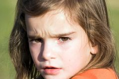Angry or wondering girl. Close up of a young girl looking at something with either anger or wonderment stock photo