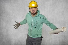 An angry worker with construction plans. Protective helmet on the head Royalty Free Stock Photos