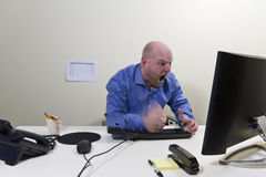 Angry Worker hit his keyboard. Angry office worker / businessman hit his computer keyboard. Keys and coffee in motion stock photo