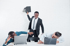 Angry worker leaving company. Firing with scandal. Firing from the company. Leaving the office. Furious ex-worker crashing his laptop. Stress at work Stock Images