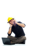 Angry workers close his ears. Angry workers wearing safety helmets close his other ears while talking on his mobile phone isolated with white background. The Stock Photo