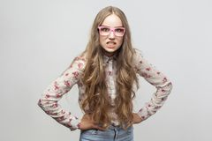 Angry young adult woman in pink eyeglasses, and shirt, looking a. T camera and roar. Studio shot. Isolated on gray background royalty free stock photos