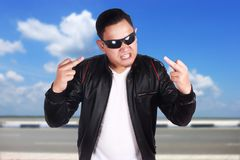 Angry Young Asian Man Shows Middle Finger. Portrait of young attractive angry Asian man wearing black leather jacket and sunglasses showing middle finger, over Royalty Free Stock Photography