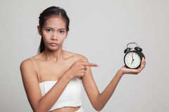 Angry young Asian woman point to a clock. Stock Photos
