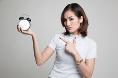 Angry young Asian woman point to a clock. Stock Image