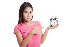 Angry young Asian woman point to a clock. Royalty Free Stock Image