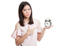 Angry young Asian woman point to a clock. Stock Images