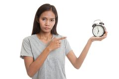 Angry young Asian woman point to a clock. Royalty Free Stock Images
