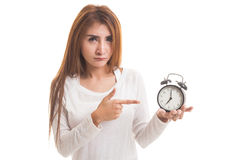 Angry young Asian woman point to a clock. Royalty Free Stock Photo