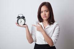Angry young Asian woman point to a clock. Royalty Free Stock Photos