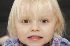 Angry young baby girl face. Angry blond young baby girl funny face Royalty Free Stock Photography