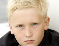 Angry Young Boy. Young blond boy with angry expression.  Close-up face, freckles, blue eyes, looks mad Stock Photos