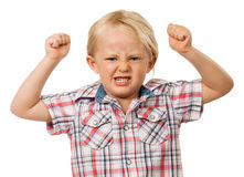 Angry young boy. A frustrated and angry young boy with fists raised in the air and pulling a face. Isolated on white Stock Photography