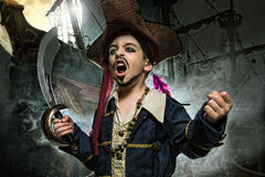 A angry young boy wearing a pirate costume. He stands on the background of the ship stock image