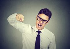 Angry young business man accusing someone royalty free stock image