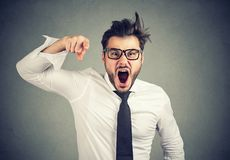 Angry young business man accusing someone screaming. Angry young mad business man accusing someone screaming looking at camera Stock Image