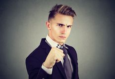 Angry young business man with closed fist looking at camera. Angry business man with closed fist looking at camera on gray background Royalty Free Stock Images