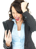 Angry Young Business Woman Screaming Down a Telephone. A DSLR royalty free image, of an attractive young business woman, screaming at telephone and pulling on Stock Photos