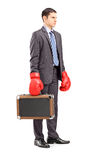 Angry young businessman holding a briefcase with boxing gloves Stock Image